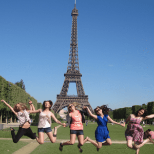 graduates jumping in front of the eiffel tower