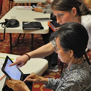 Woman assisting another woman with tablet