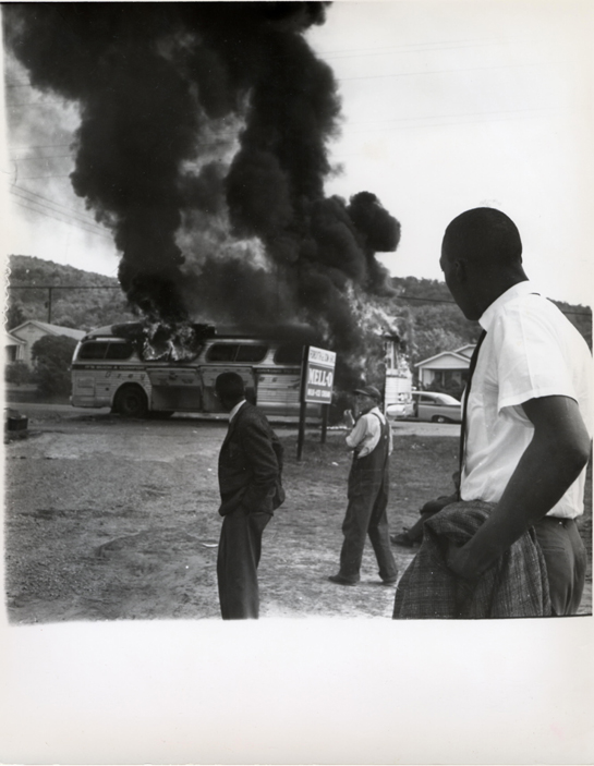 Three men look on at the burning bus as black smoke billows out from the sides