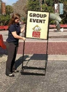 Nicole Morrison sets up a sign for a group event at the zoo