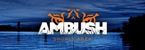 AMBUSH logo with tiger eyes over Muscle Shoals bridge and water
