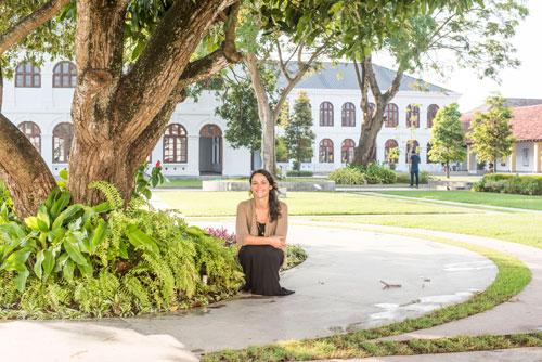 Carmen Britton squatting under a tree