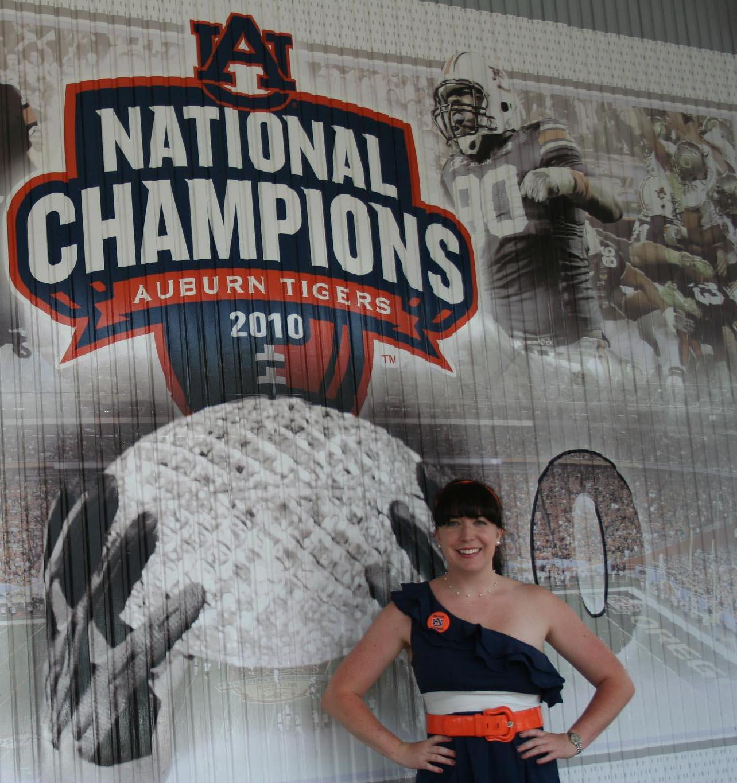 Tori Allen standing in front of Auburn's National Championship Logo