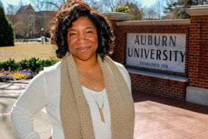 a photo of Erin Hutchins by the Auburn sign