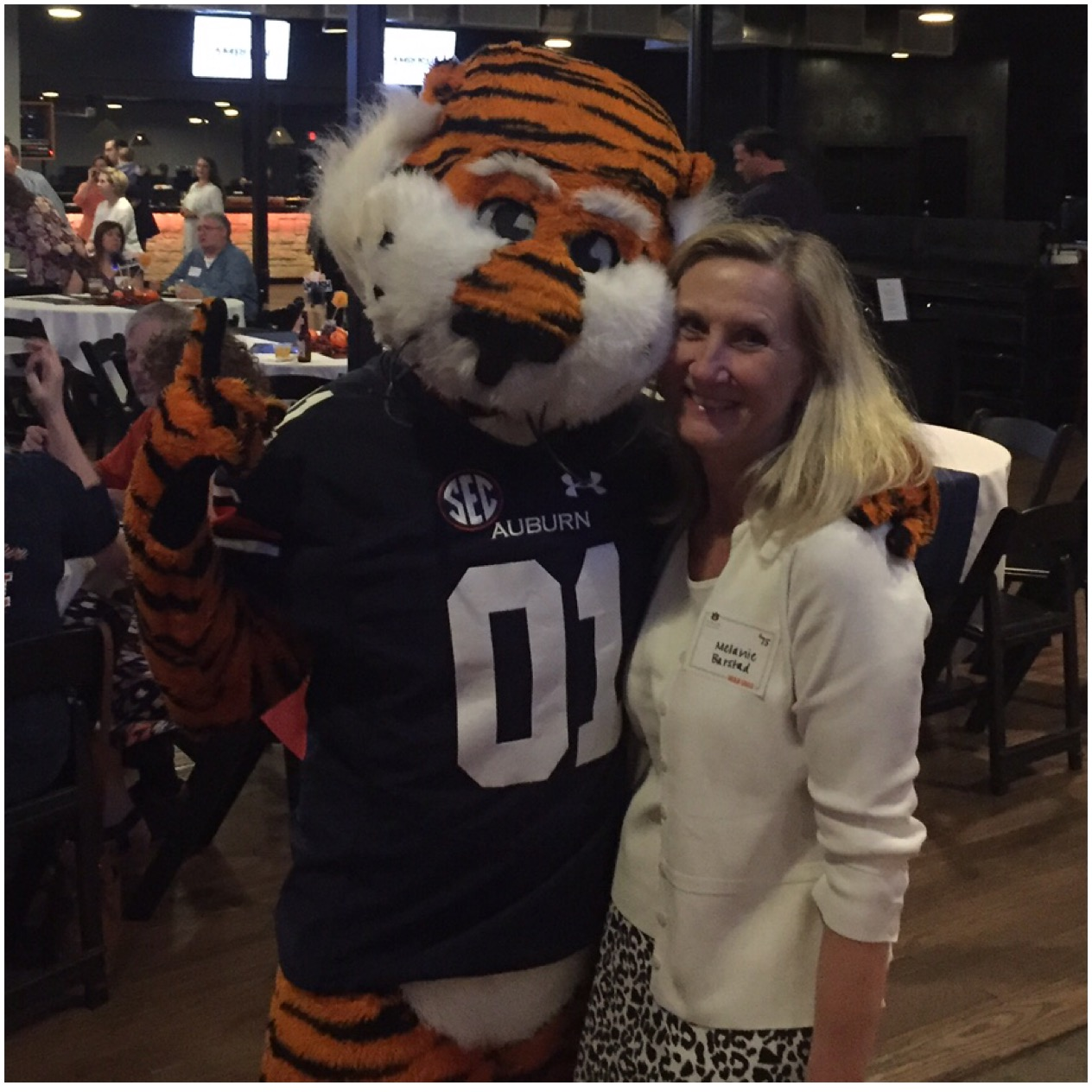 Melanie Whatley Barstad '75 taking a photo huging Aubie