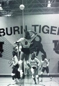 Women hitting volleyball over net