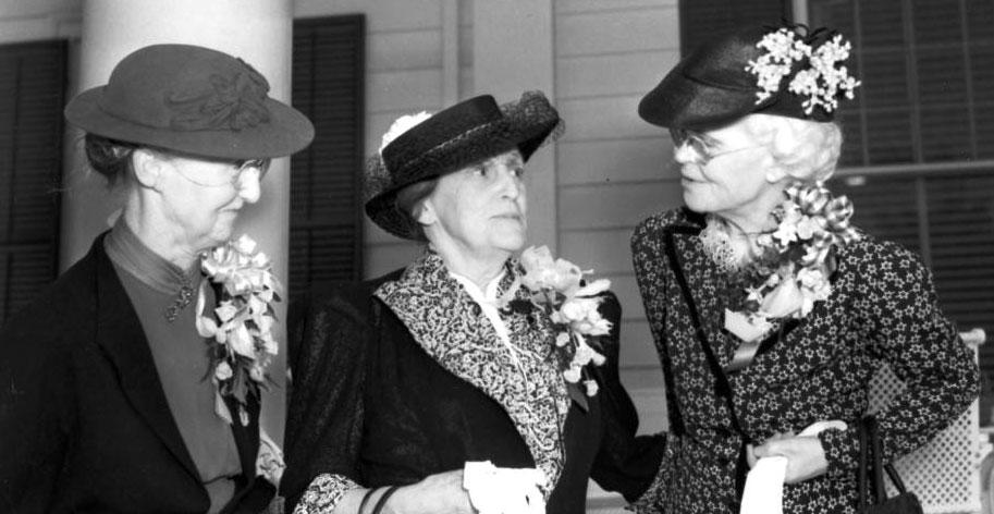 3 older ladies standing on porch