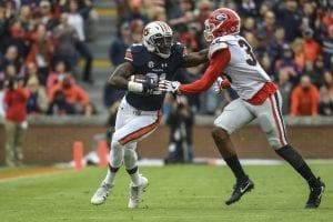Auburn player stiff-arming a Gerogia player