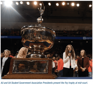 AU and UA Student Government Association Presidents present the Foy trophy at mid-court.