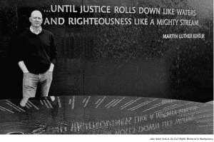 """York in front of Martin Luther King Jr. quote """"...Until justice rolls down like waters and righteous like a mighty stream."""" at the Montgomery Civil Rights Museum"""