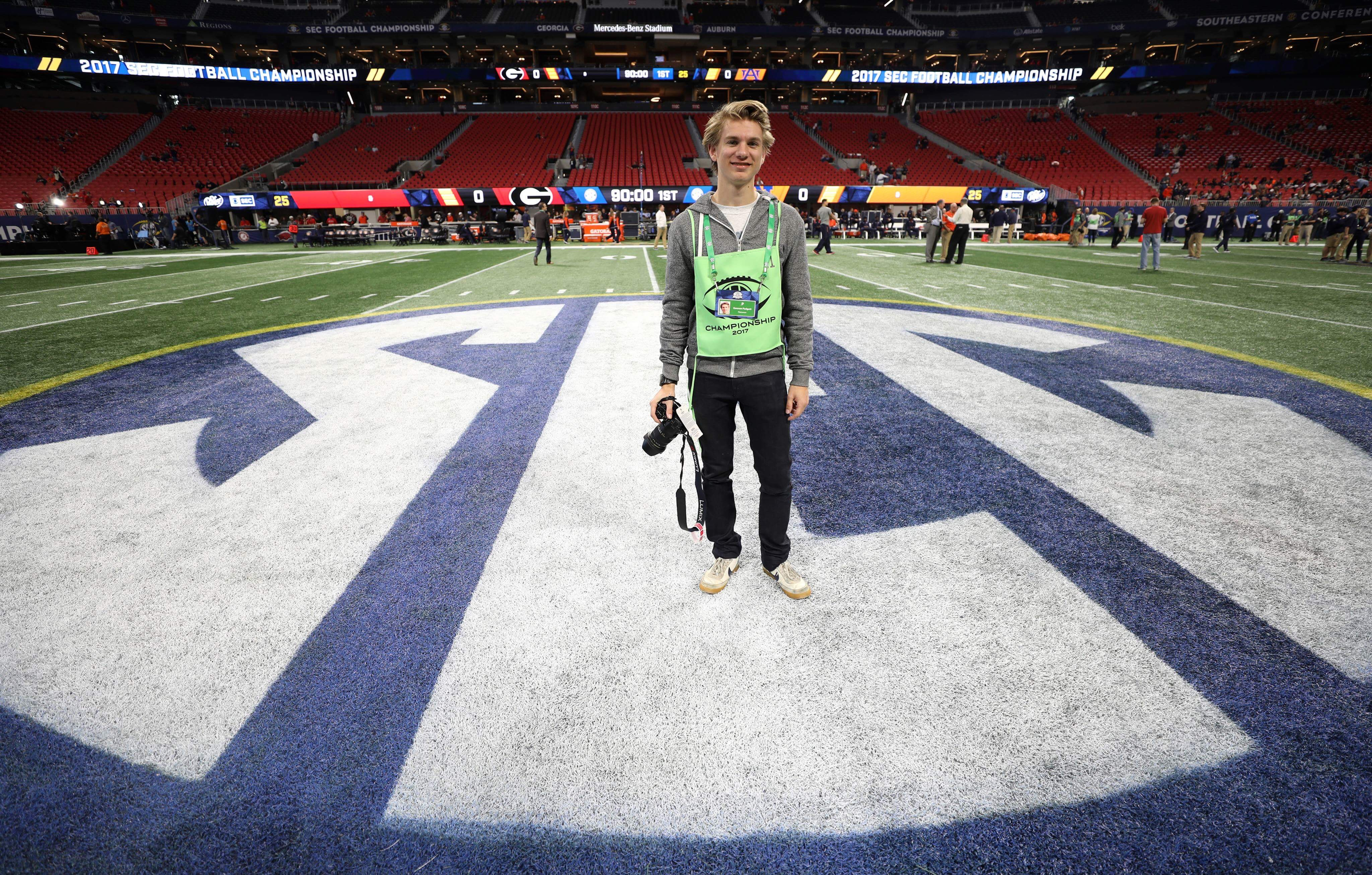 Padgett stands on the SEC emblem on the field prior to the SEC Championship Game holding a camera.