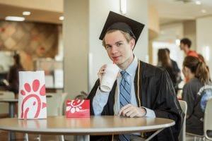 Padgett sips on a drink from Chik-fil-A while in his graduation robe and cap.