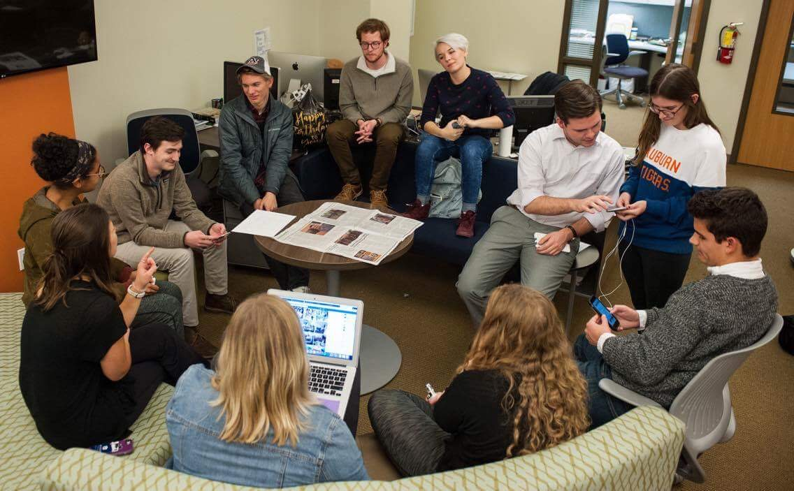 Padgett sits in a circle with 10 other members of the Plainsman's editorial staff working on the paper.