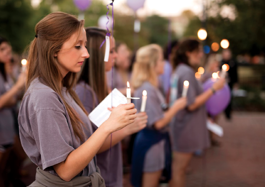 Auburn students light candles at a domestic violence vigil on campus.