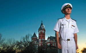 Cole Burton in his Navy uniform standing in front of Samford