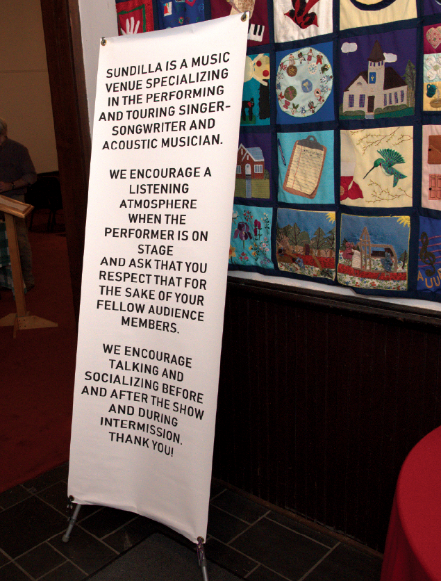 """A lobby sign explains how Sundilla's """"listening room"""" is all about the music and musicians. It reads Sundilla is a music venue specializing in the performing and touring singer-songwriter and acoustic musician. We encourage a listening atmosphere when the performer is on stage and ask that you respect that for the sake of your fellow audience members. We encourage talking and socializing before and after the show and during intermission. Thank you!"""