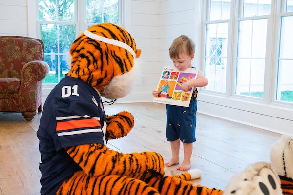 baby reading book to Aubie