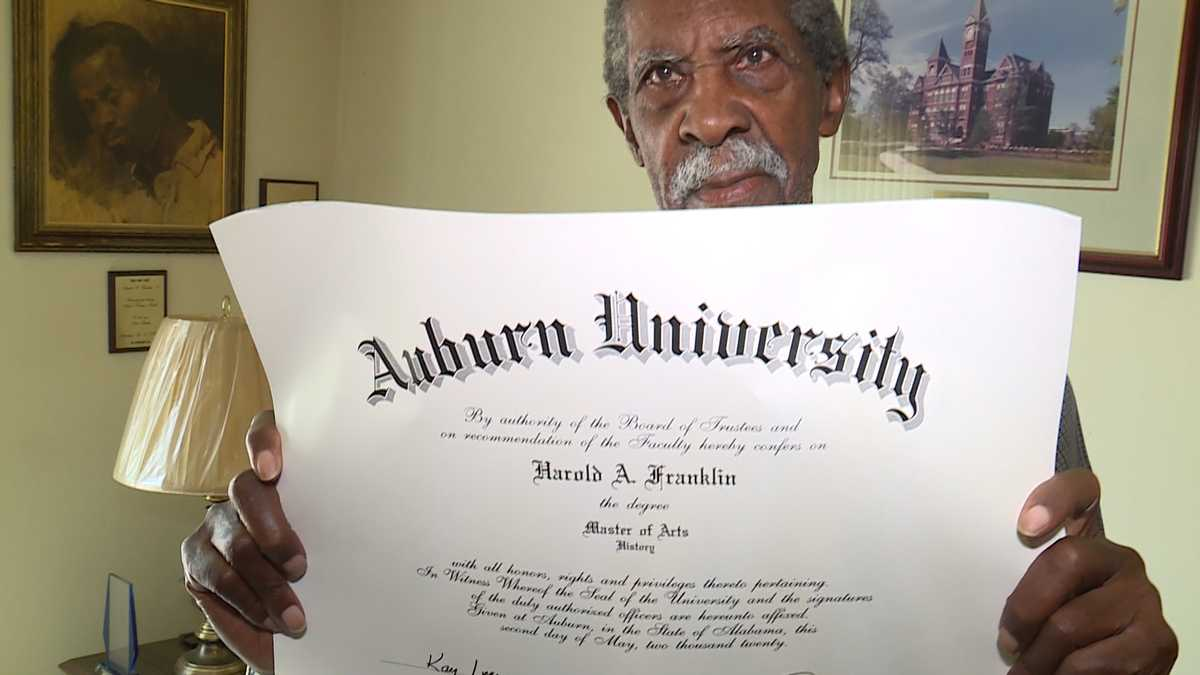 Dr. Harold Franklin holding diploma