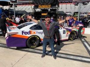Brannon standing infront of racecar