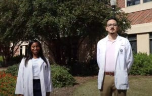 two students standing infront of Harrison School of Pharmacy building