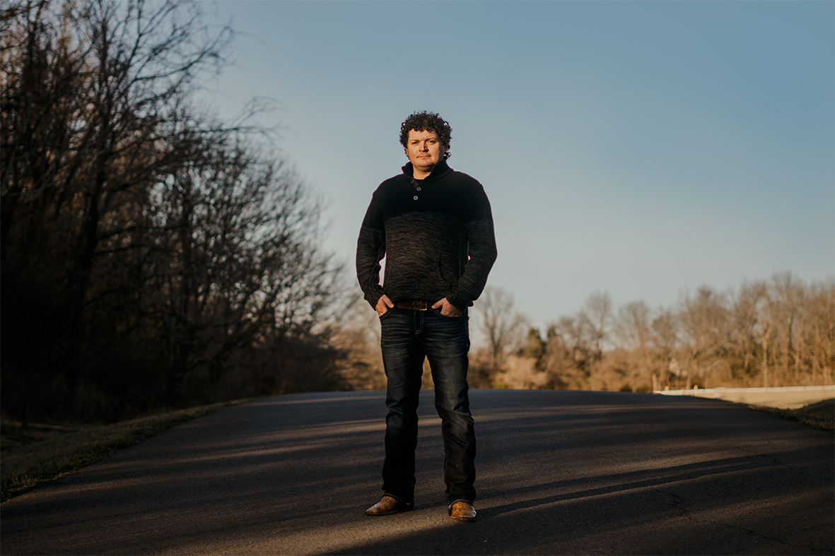Dustin Herring stands in the road for an album cover photo.