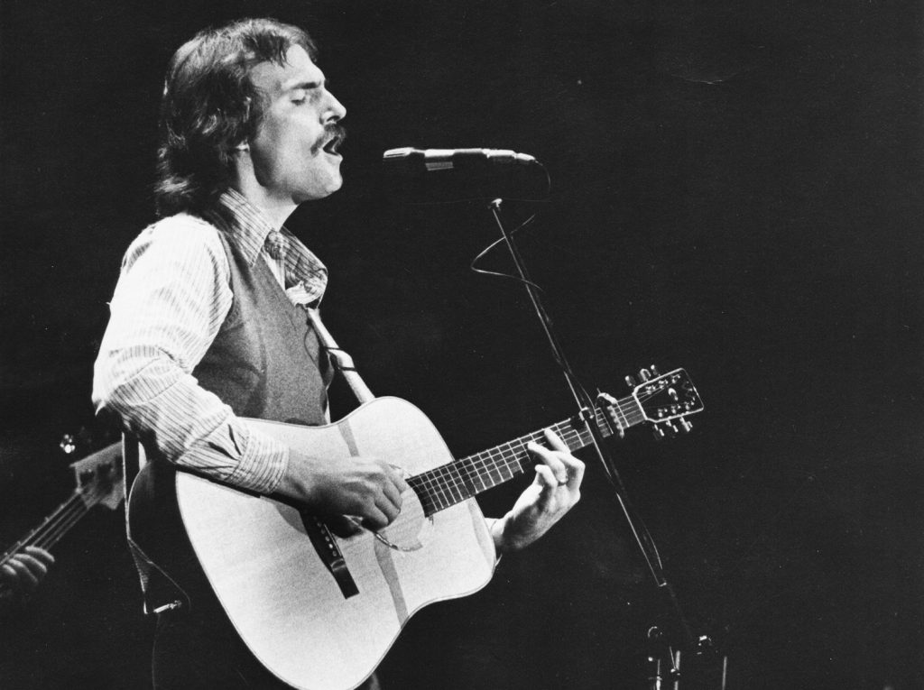 James Taylor strumming his guitar on stage while singing into microphone