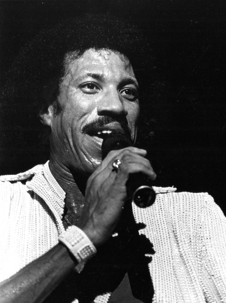 Lionel Richie on stage singing with microphone in his right hand
