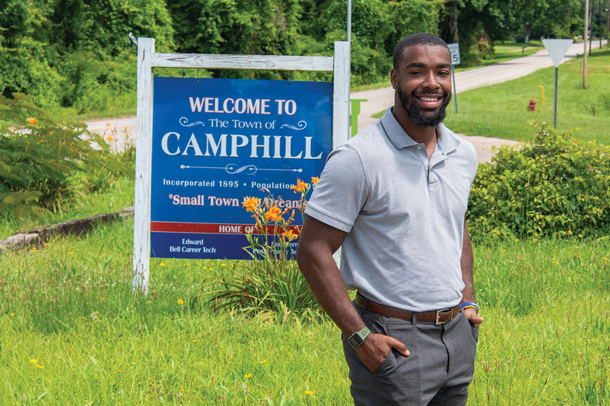 Messiah Williams-Cole standing in front of Camphill Sign