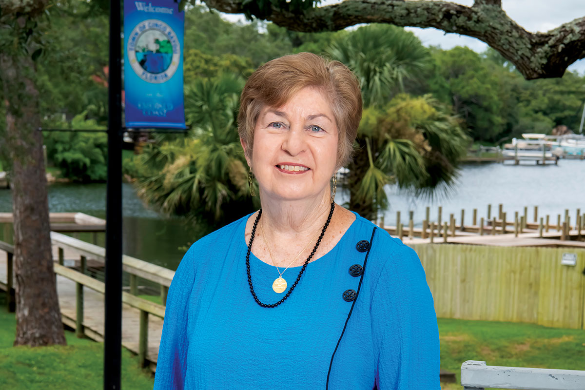 Jean Hood standing in front of palm trees wearing blue blouse