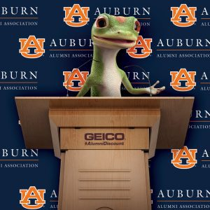 Geico Sponsor graphic with gecko standing behind podium