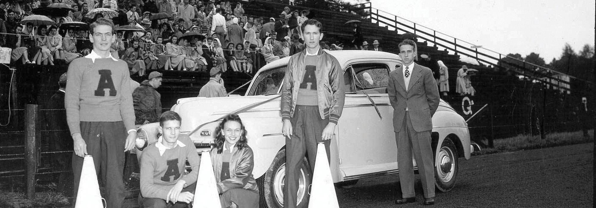 Auburn Cheerleaders leaning on an old car